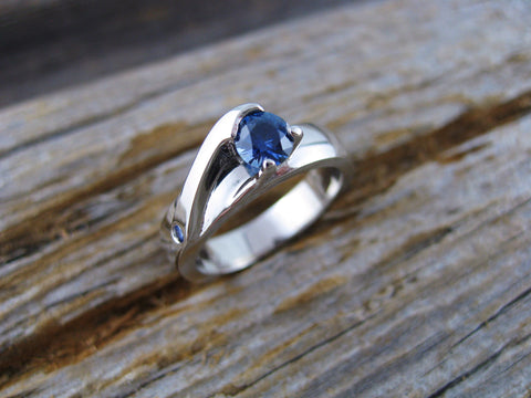 this wave like ring is in 14K palladium white gold set with two medium blue Montana sapphires