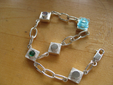 <p> emma brick bracelet: sterling silver bracelet with inset emerald works with lego</p>