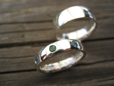 derek and morena set: two sterling silver bands,  engraved hers is set with one emerald and two topaz