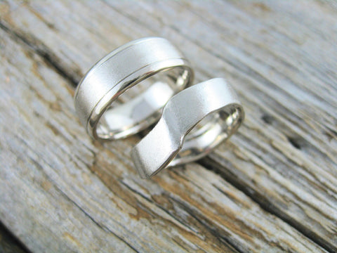 derrick and valerie wedding bands: Hers 14k palladium white gold designed to nestle beside her isle de madeleine engagement ring with a texture of a sandy beach. His 14k palladium white gold designed to be simple yet have similar features to her band.