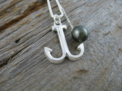 this fun necklace in sterling silver is not only an anchor but also an initial necklace if you look closely you can see a J for jo-ann and also a G for gerry :) there is also a black tahitian heirloom pearl.