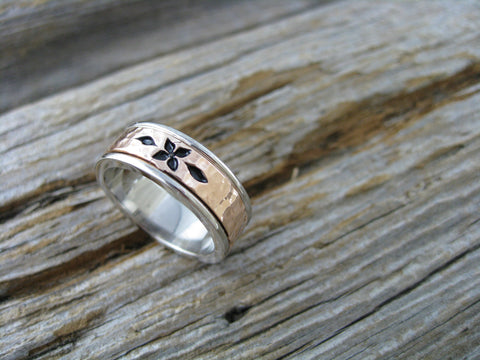 14K palladium white gold and a centre band of 14k rose gold with a dogwood pattern on it.
