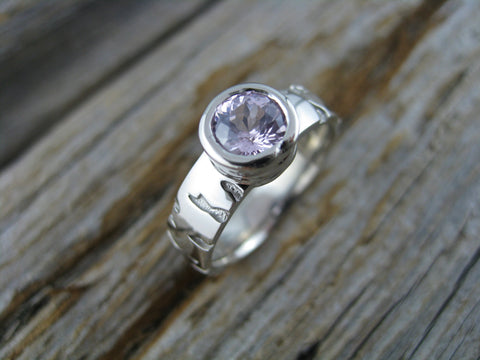 a gorgeous light pink sapphire set in 14K palladium white gold with a custom birch pattern as her favourite tree is birch :)