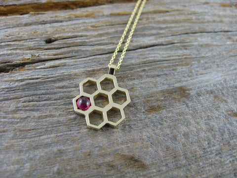 "<meta charset=""utf-8""><span>Sarah custom 14k yellow gold honeycomb necklace is set with a cabochon ruby (her birthstone) for her birthday.</span>"