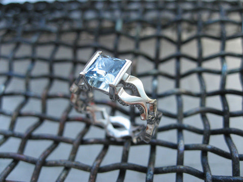 <p>andi ring: gorgeous princess cut aqua set in a custom 18k palladium white gold band. Opening and closing brackets. One does not work without the other a perfect subtle symbol for a couple of bibliophiles.</p>