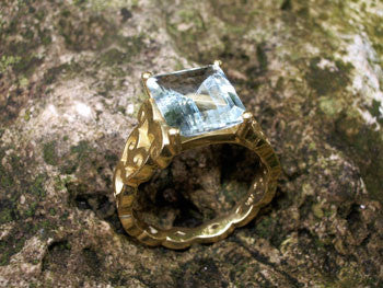 <p>ann ring:  emerald cut aqua in 18k yellow gold cocktail ring</p>