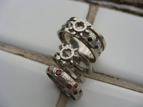 <p>geoff and darien set: 14k palladium white gold - lego gear steampunk styled rings - hers with wedding band insert with garnets set into squid tentacles - his with sapphires set into moon scape</p>