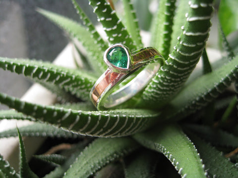 <p>huan ring: pear shaped emerald set in a sterling silver and copper band</p>