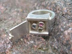 <p>gens spring ring: three coloured sapphires set in white gold and on springs that pop out when lids is opened - ring is made of sterling silver</p>
