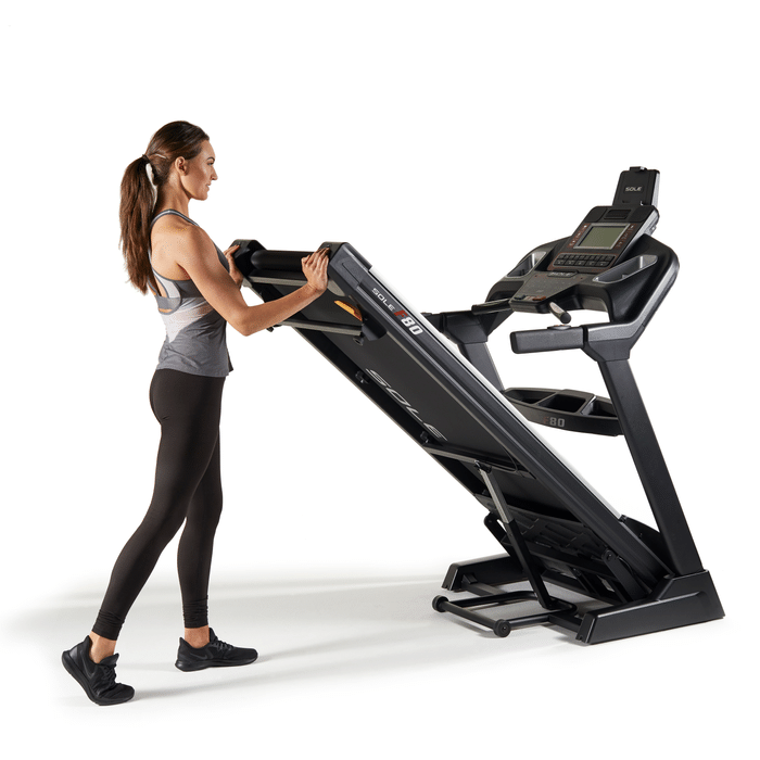 Lady folding the Sole F80 treadmill deck up