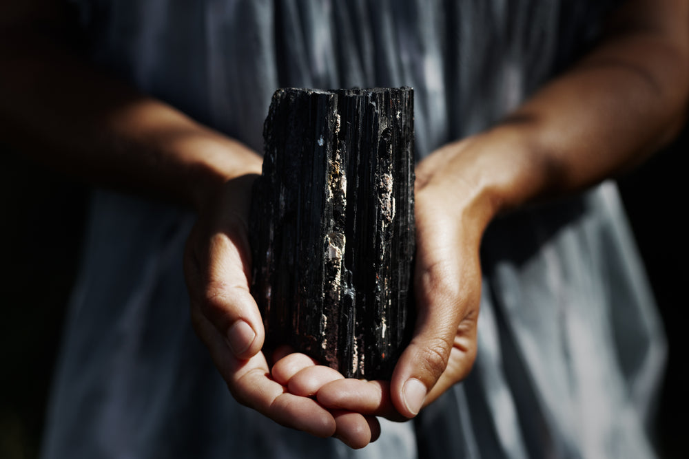 person holding a large black tourmaline crystal