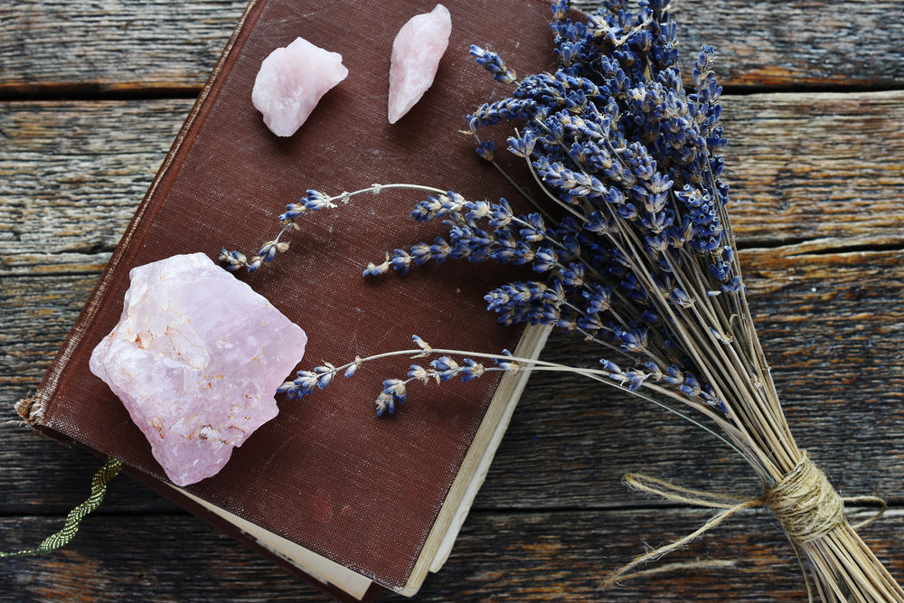 Scattered Rose Quartz crystals near some flowers.