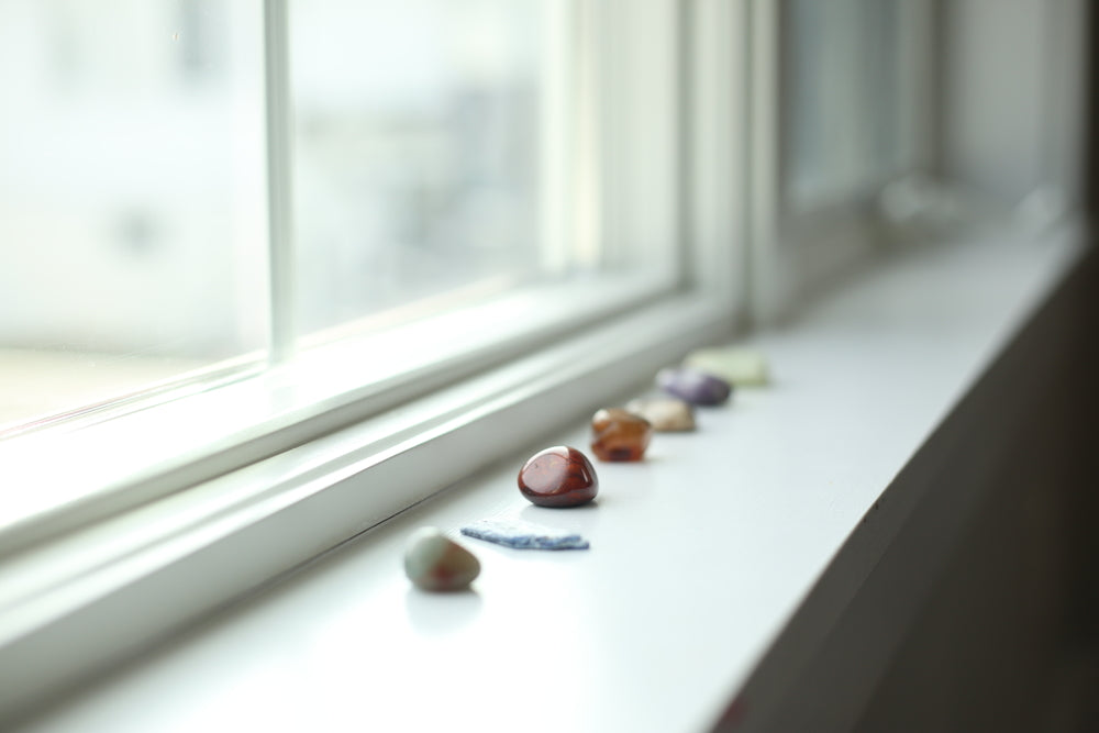 A collection of healing crystals on the windowsill.
