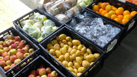 an assortment of fruits and vegetables at a neighborhood pop-up event