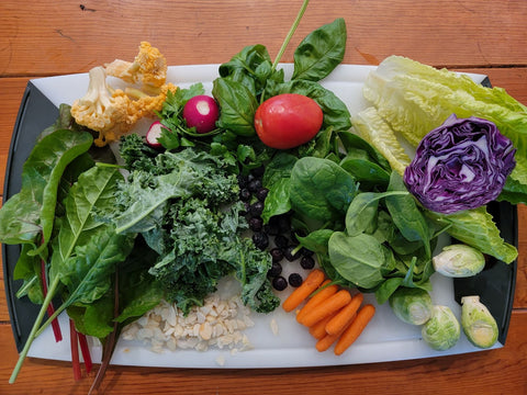 cauliflower, chard, kale, almond slivers, spinach, radishes, tomatoes, carrots, brussels sprouts, and purple cabbage cut and ready on a serving platter