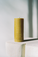 Dark Yellow Beeswax Pillar Candle with Logo Happy Society on white pillar.