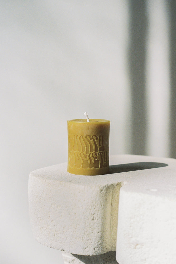 Dark Yellow Beeswax Candle, unlit, with logo Happy Society. Sitting on a white pillar.
