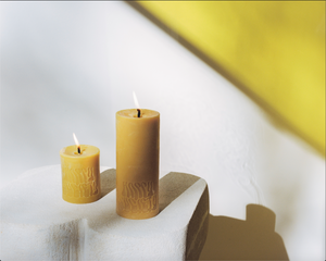 2 Dark Yellow Beeswax Pillar Candles with Logo Happy Society on white stone. Both candles lit, one large one small.