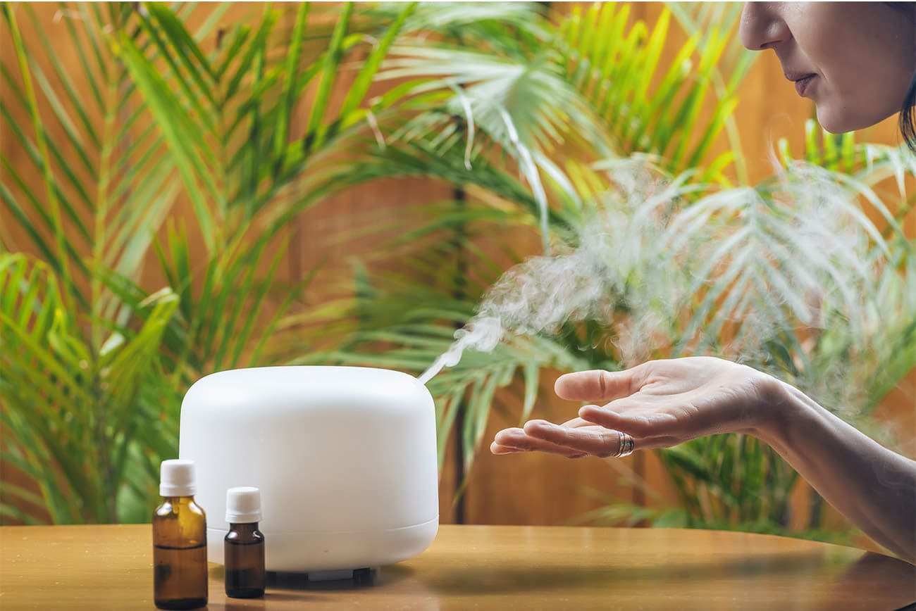 Woman enjoying the smell of essential oil from an aroma diffuser
