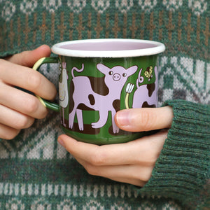 Green, Pink, White and Black Enamel Friends Not Food Design Mug by Vegan Illustrator Eva Stalinski Featuring Pigs, Chickens and a Cow. Being Held by Eva Wearing a Knitted Green Sweater Jumper.Produced by Family Owned Polish Factory Emalco Enamelware in 2020.