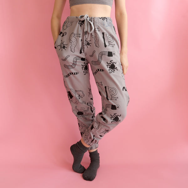 Hand Screen Printed Black and Grey Bug Insect Pattern Sweatpants made and modeled by Eva Stalinski on a bright pink background