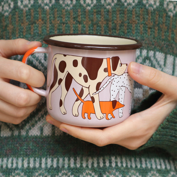 Illustrator Eva Stalinski Wearing a Knitted Green Sweater Jumper, Modeling a Pink, Orange, Cream and Brown Enamel Dog Design Mug Featuring Great Dane, Dachshund, Dalmatian, Pug, Pointer and Jack Russell Dogs, 2020. Produced by Family Owned Polish Factory Emalco Enamelware