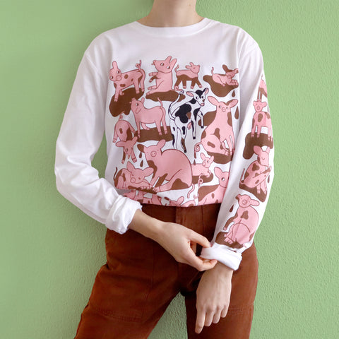 White Hand Screen Printed Pigs in Mud Illustration Long Sleeve in Organic Cotton Made and Modeled by Print Maker Eva Stalinski Against a Green Background, 2020