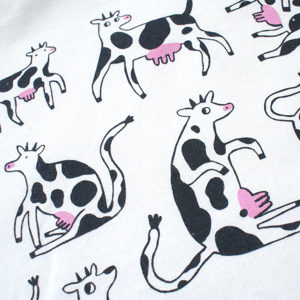 Screen printed white sweatshirt with happy cows illustration by Eva Stalinski close up big front print