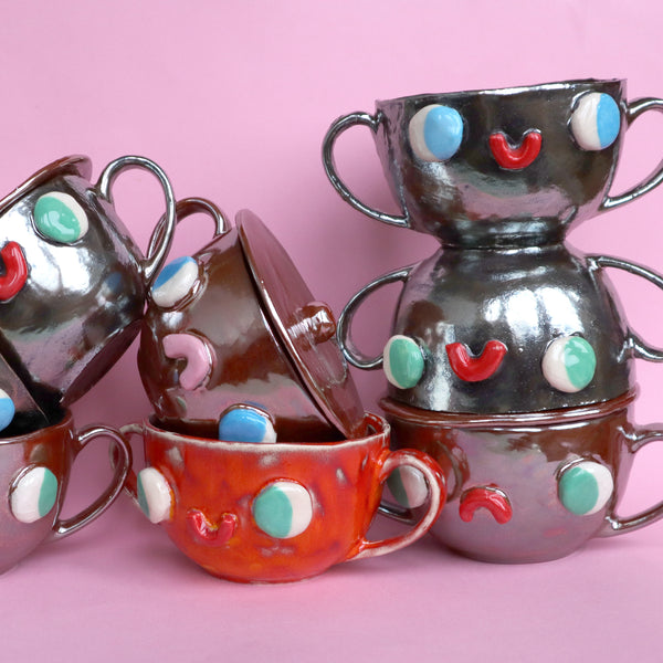 Stack of Silver, Copper, Orange, Two Eared Slipcast Ceramic Mugs with Faces by Illustrator Eva Stalinski, 2020. Anthropomorphic Silver Mugs.