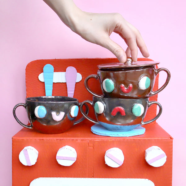 Stack of Silver, Copper Two Eared Slipcast Ceramic Mugs with a Face by Illustrator Eva Stalinski, 2020. Anthropomorphic Mugs on Orange, Blue and Pink Cardboard Toy Kitchen Prop