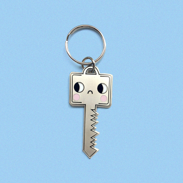 sad, matte silver, plated keychain in the shape of a key by eva stalinski single key