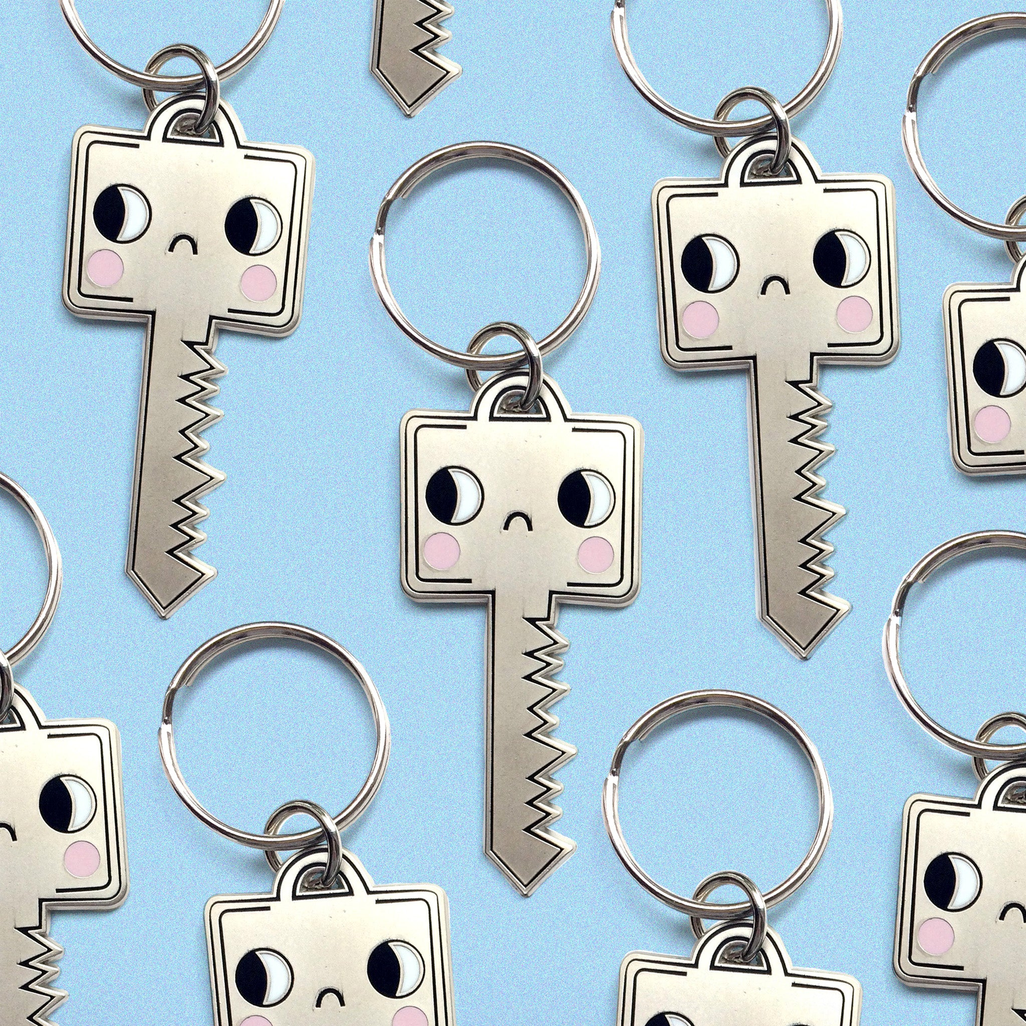 sad, matte silver, plated keychain in the shape of a key MULTIPLES