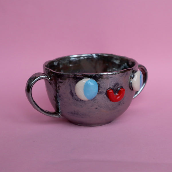 Front View of Rotating Gif Video of Pewter Silver Two Eared Slipcast Ceramic Mug with a Face by Illustrator Eva Stalinski, 2020. Anthropomorphic Silver Mug.