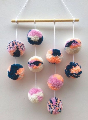 photo of wall hanging made of pom poms
