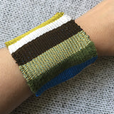 "Woven bracelet created on our Purl & Loop bracelet loom.  This one is 2"" wide and made with silk threads."