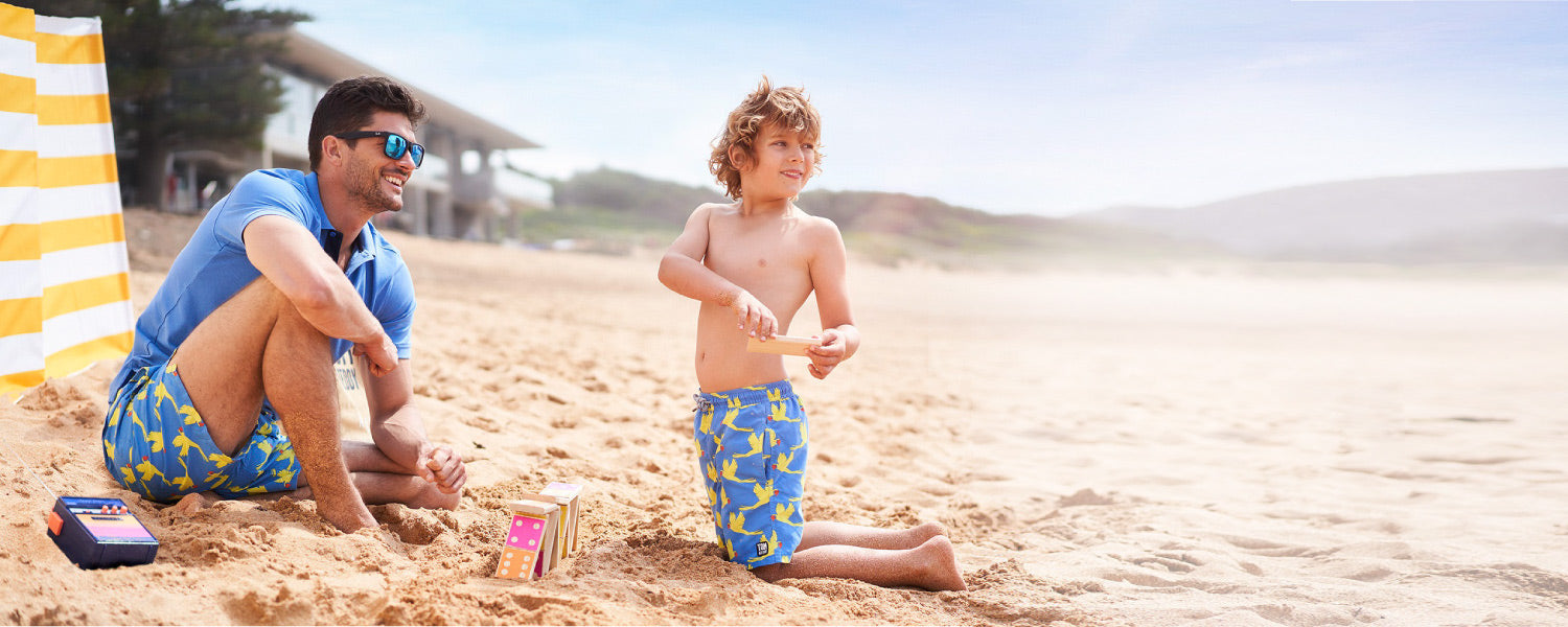 Tom and Teddy Swim shorts in matching sizes for father and son shown on beach with new octopus print twinning boardshorts in blue.