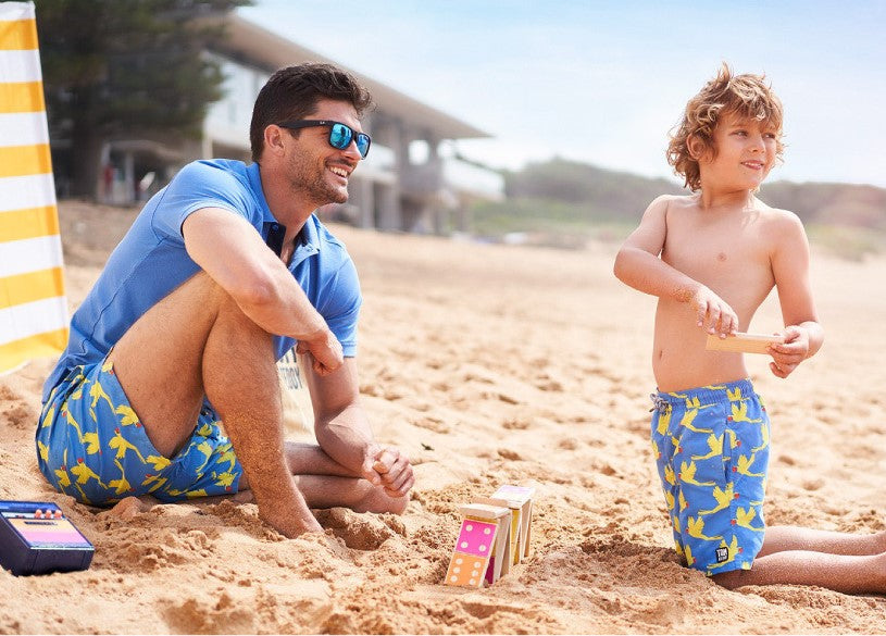 Tom and Teddy Swim shorts in matching sizes for father and son shown on beach with new bright green and blue octopus print twinning beachwear swim trunks