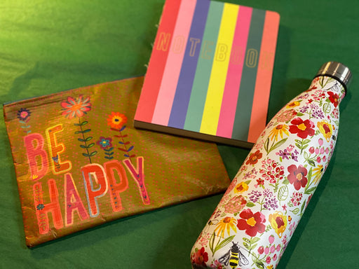 "Do you know someone who could use a little sneak peak at spring for a quick pick me up? This gift set is the perfect thing! It comes with a rainbow themed notebook, a ""Be Happy"" pouch, and a beautiful floral and bee print thermos - good for either hot or cold drinks.  The pouch is from Natural Life and is made from 80% recycled plastic bottles."