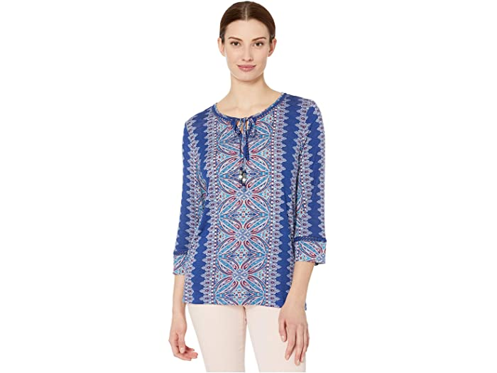 The TRIBAL® 3/4 Sleeve Henley Top embraces a boho-chic aesthetic with an allover abstract print, ladder-stitch trims at the collar and sleeves, and a split neckline with self-tie accent. Blouse is featured on a stretch rayon fabrication. Three-quarter length sleeves. Pullover styling. Straight hemline with side vents. 95% rayon, 5% spandex. Machine wash cold, line dry.