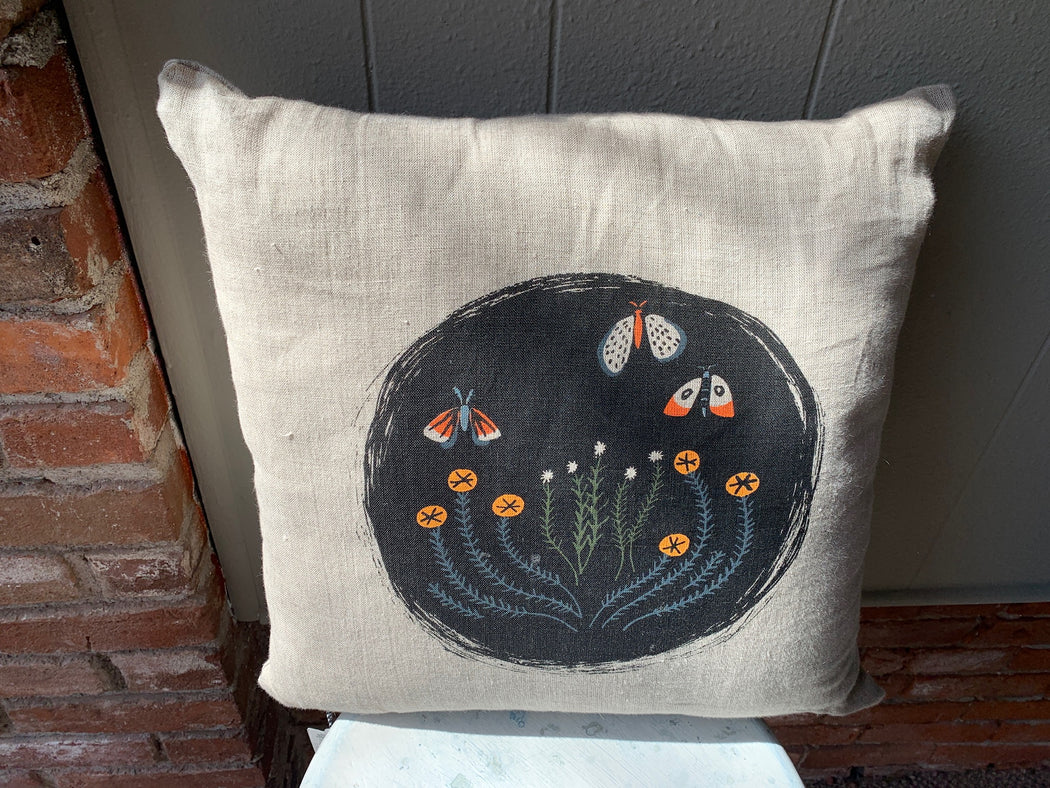 Black circle with moth and flower print. Colors include black, orange, and navy blue.