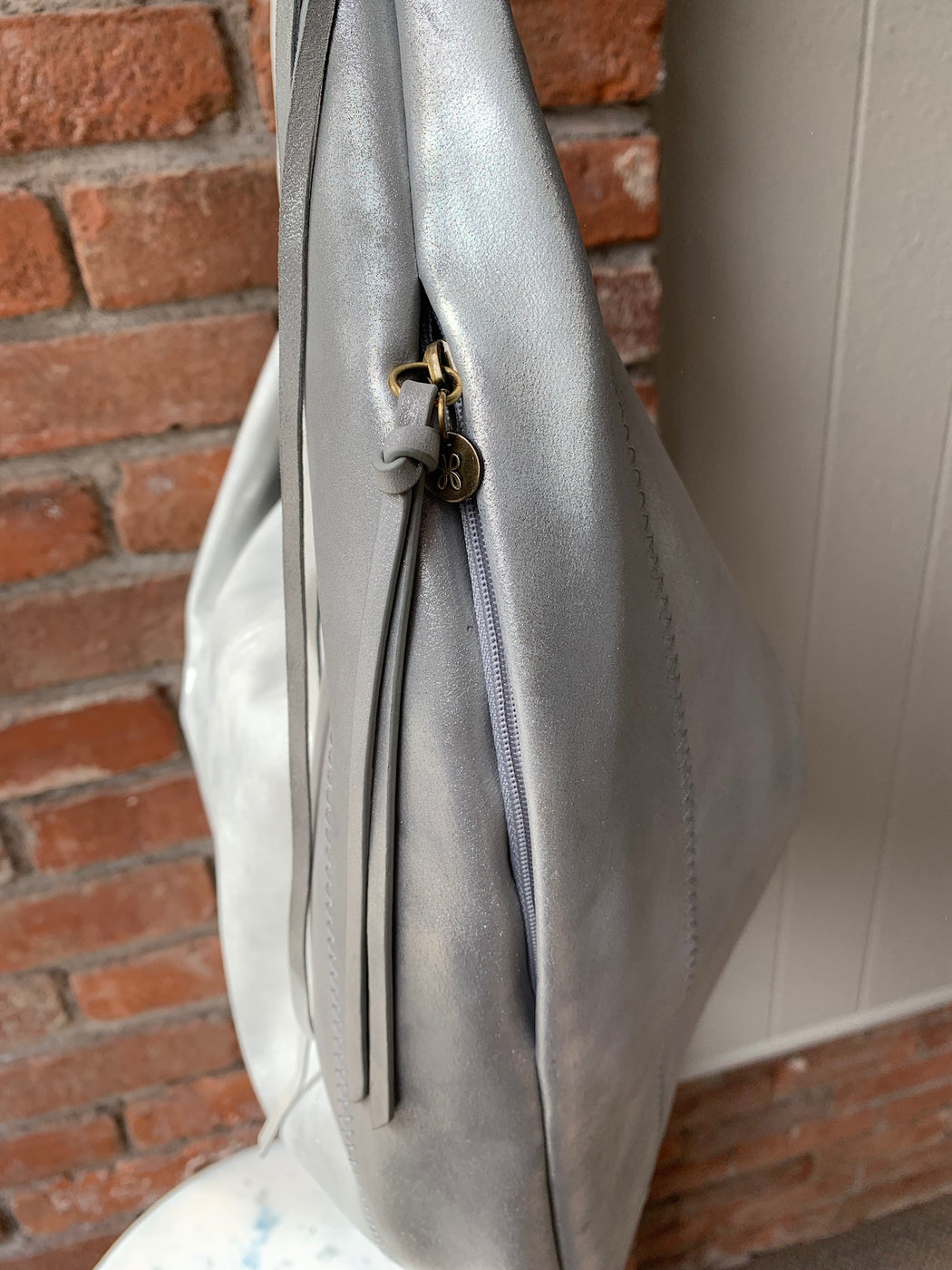 "Boho-tinged and reminiscent of the 70's, the Kindred hobo shape is crafted in velvet hide with the perfect amount of slouch, free-spirited tassels at each side, plus a whipstitched strap for all the rock n' roll vibes.  Single top handle  Zip top closure  Exterior features back zip pocket  Interior features zip wall pocket, pen slot, and 2 slip wall pockets  Approx. 13"" H x 18"" W x 1"" D  Approx. 12"" strap drop  Color: Northern Lights  Original Price - $328.00"