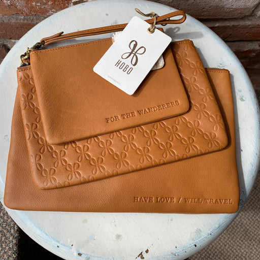 "3 separate zip pouches with detachable wristlet strap   Top zip closures  Exterior features embossed text (pouch 1 and 3), genuine cal hair and leather construction (pouch 2)   Dust bag included   Approx. 4.5"" H x 6"" W (pouch 1)   Approx. 5.5"" H x 8"" W (pouch 2)  Approx. 6.5"" H x 10"" W (pouch 3)   Approx. 6"" strap drop  Color: Natural  Original Price - $138.00"