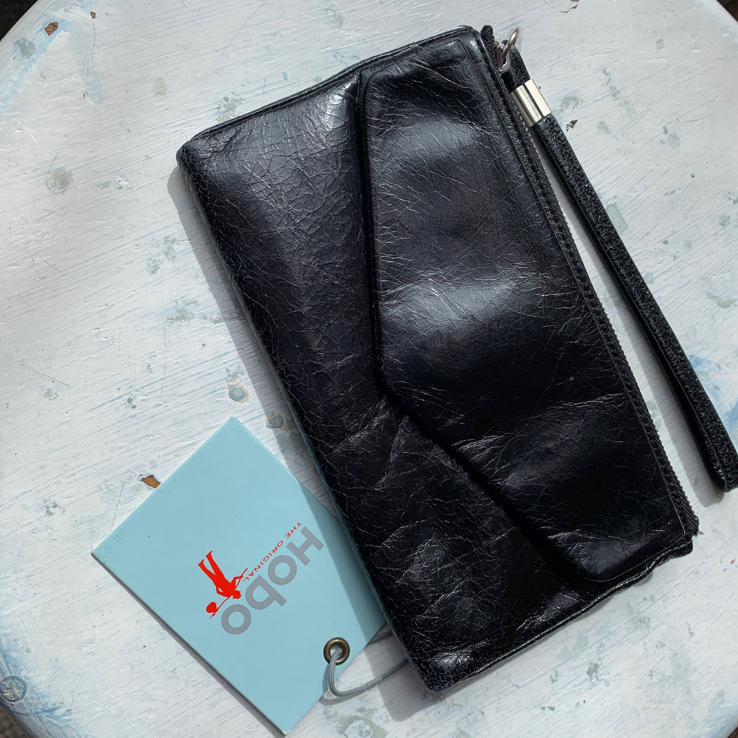 "100% Leather Imported Synthetic lining Zipper closure 4"" high 6.75"" wide Top zip closure Exterior hidden magnet flap pocket 3 credit card slots ID holder Wrist strap Color: Black Original Price - $88.00"
