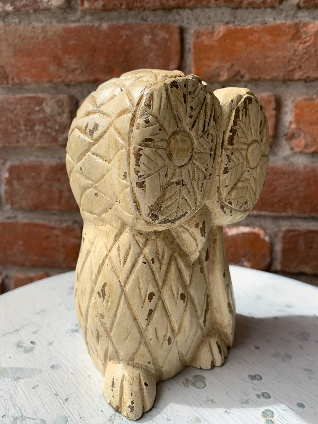Distressed, cream colored owl statue.