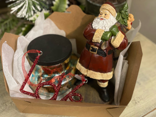 "Bring some Christmas Cheer to someone you love! This box comes with a Santa, a Candle, and a red, beaded ornament that says ""Love""."
