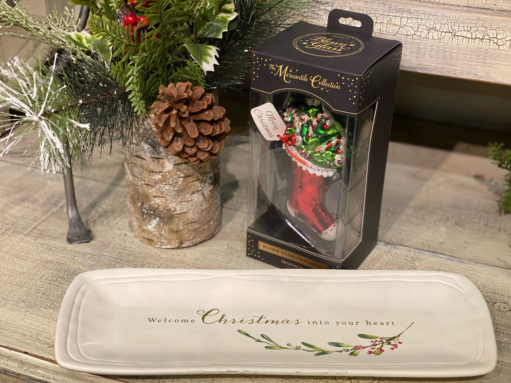 "This little gift bundle comes with a platter that says, ""Welcome Christmas into your heart."" The platter measures 5 1/4"" x 14"". It is microwave and dishwasher safe.   One of the primary symbols of Christmas cheer is the candy cane, and the Candy Cane Stocking Blown Glass Ornament, complete with decorative glitter, is sure to liven up the tree of any household."
