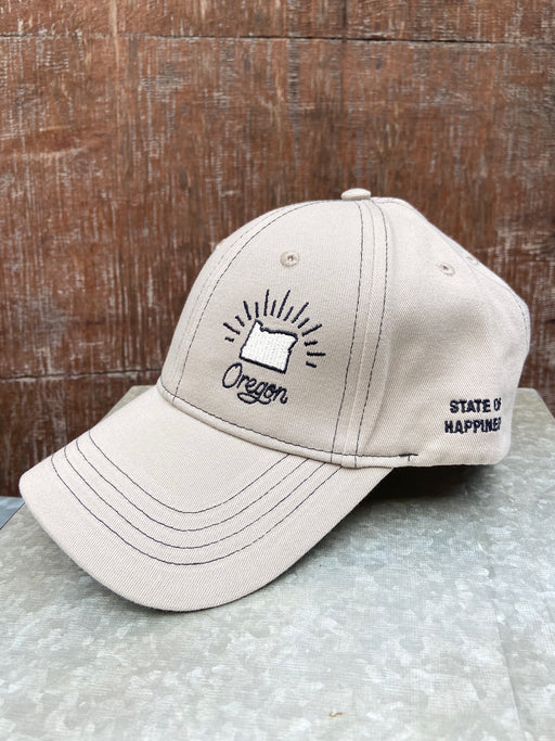 Tan ball cap with black stitching. Adjustable back with slide buckle.