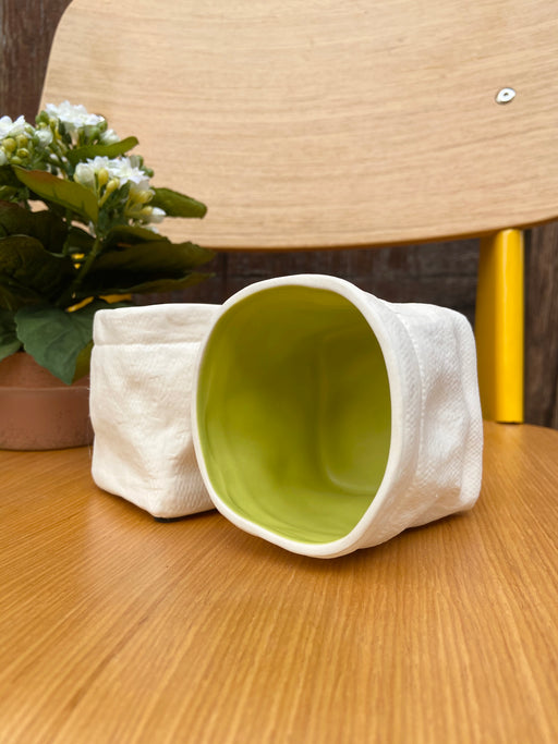 Ceramic container for plants, pencils, or make-up. Off-white outside with chartreuse inside.