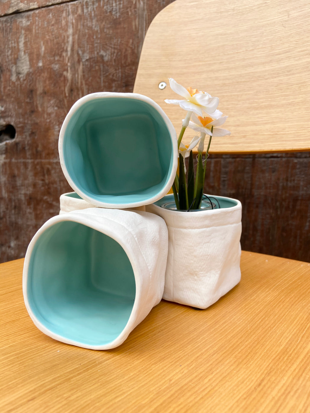 Container that looks like a bag but is made of ceramic! Off-white outside with aqua inside.