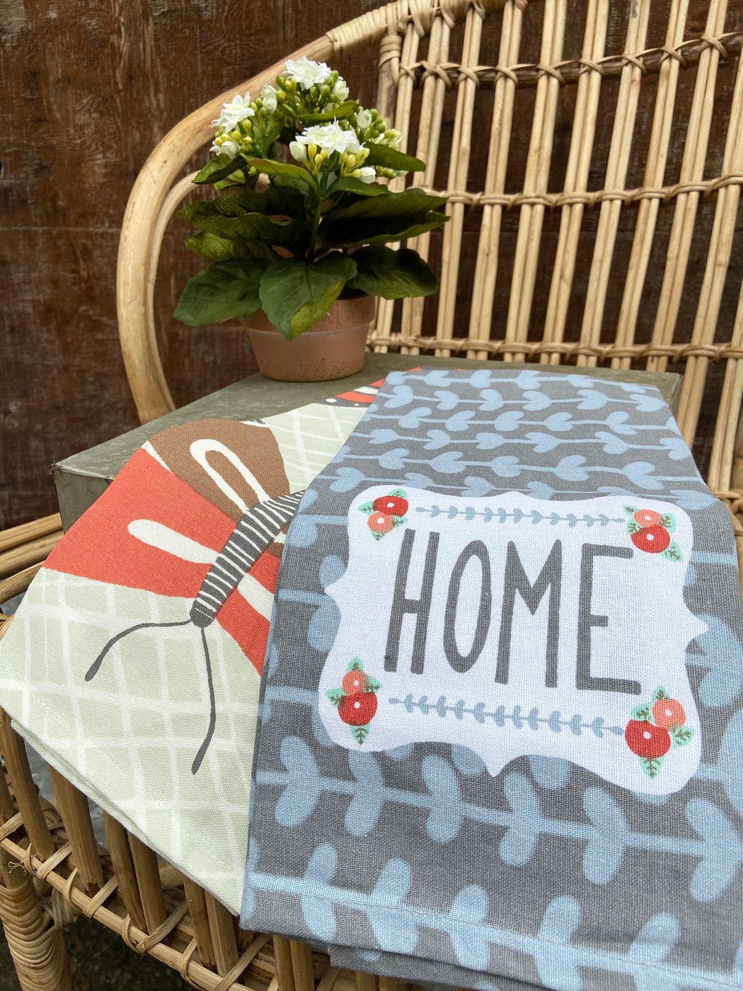 "Set of two kitchen towels. One says ""HOME"" in block letters.  It is grey, with a light blue pattern and a butterfly. The second towel is a large butterfly print, in the same color scheme. The towels are grey, blue, sage, brown, and rust."